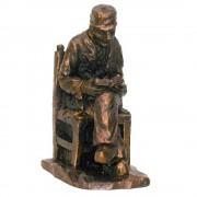 Beeld Opa lezend op stoel