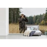 Fotobehang vinyl - Een man met verrekijker gaat op jacht in hoog gras breedte 525 cm x hoogte 350 cm - Foto print op behang (in 7 formaten beschikbaar)