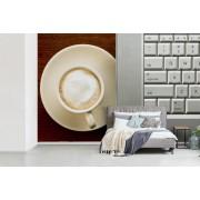 Fotobehang vinyl - Kopje cappuccino staat naast een laptop breedte 450 cm x hoogte 300 cm - Foto print op behang (in 7 formaten beschikbaar)