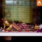 Archies red and golden polyresin decor reclining Buddha showpiece with traditional head wear lotus base